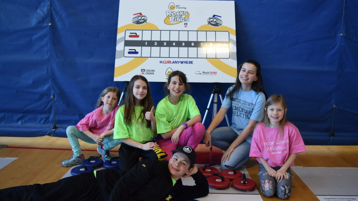 Curlers pose in front of Rocks & Rings sign