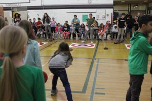 Students gather around FloorCurl mat at a tournament