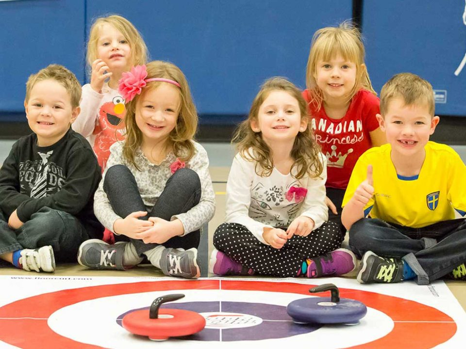 Kids sit behind curling mat