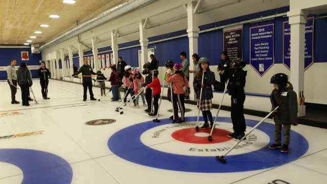 Kids stand on curling ice with curling brooms